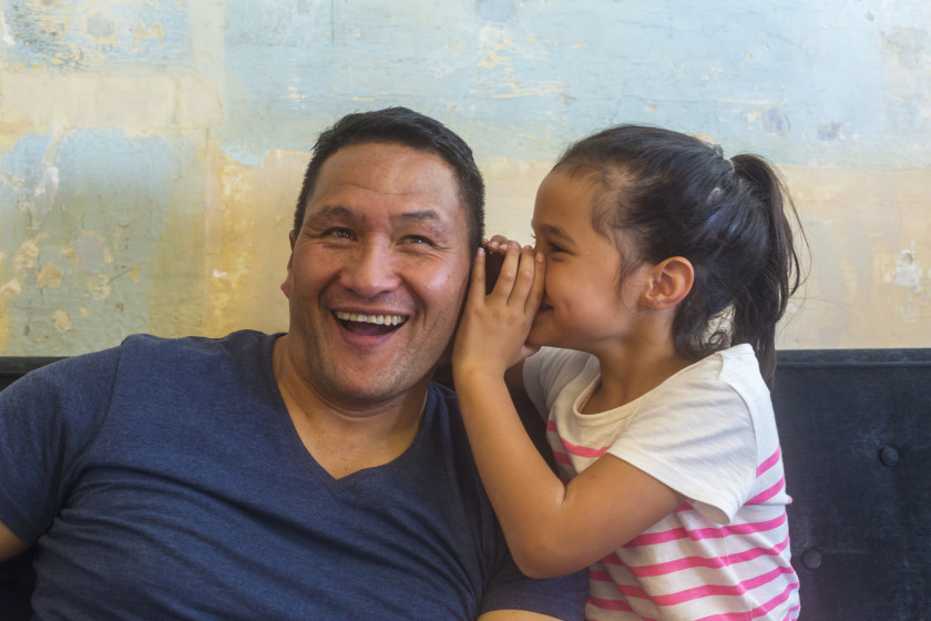 Decorative image: Maori dad and daughter on brown couch shown from waist up with daughter whispering in father's ear and father exclaiming. Girl wears a white t-shirt with pink stripes and father a blue t-shirt.