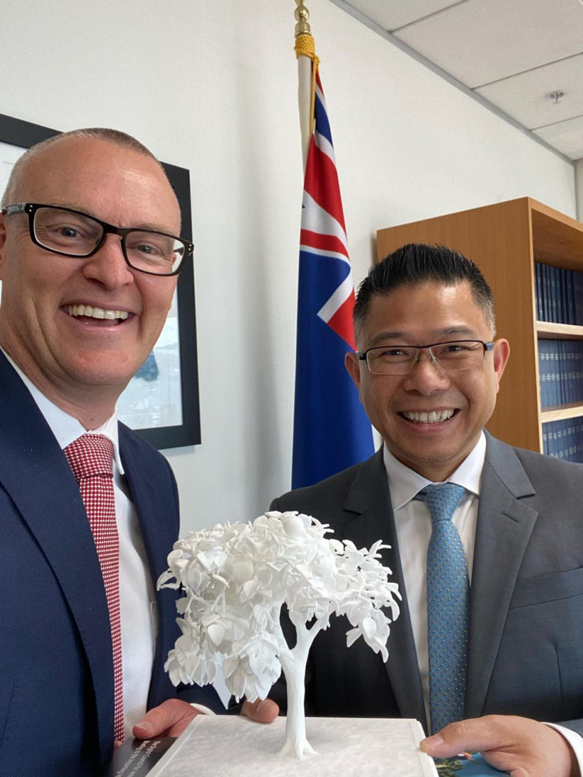 Mitchell Pham (right) and Hon Dr David Clark (left) hold a small white 3D printed tree between then. NZ flag sits in the background..